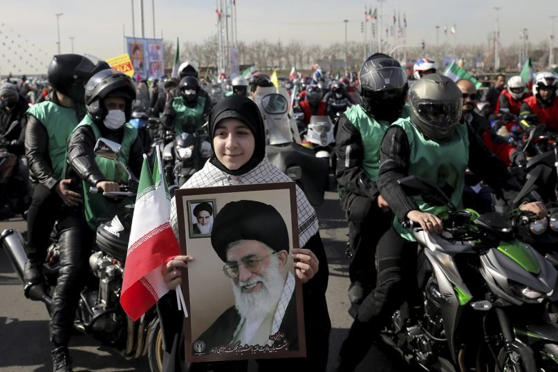 An Iranian woman holds a portrait of Iranian Supreme Leader Ayatollah Ali Khamenei during a rally marking the 42nd anniversary of the 1979 Islamic Revolution, in Tehran, Iran, Feb. 10, 2021. (AP Photo/Ebrahim Noroozi)