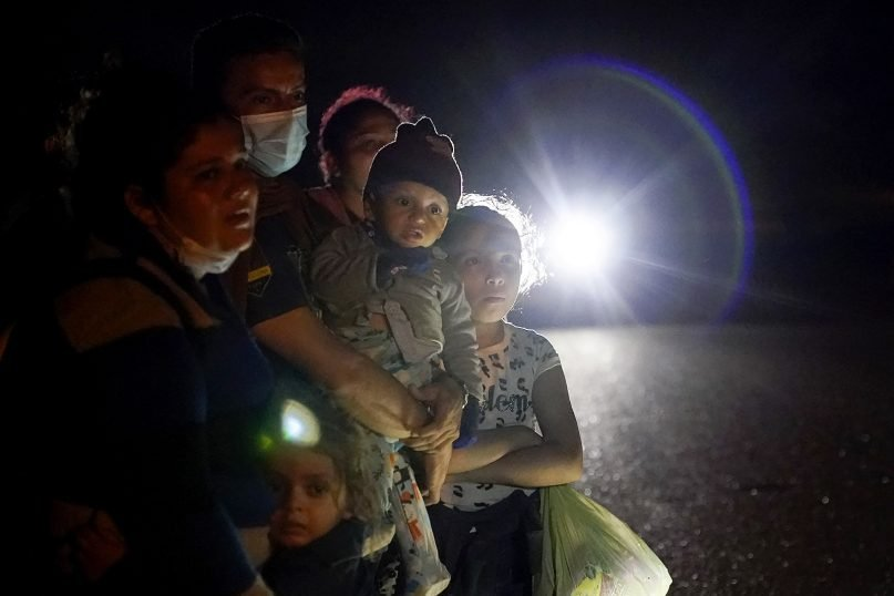 A group of migrants mainly from Honduras and Nicaragua wait along a road after turning themselves in upon crossing the U.S.-Mexico border, in La Joya, Texas, May 17, 2021. The Biden administration announced Tuesday, June 15, 2021, that it was expanding a newly-revived effort to bring Central American children to the United States to reunite with parents legally living in the country. (AP Photo/Gregory Bull, File)