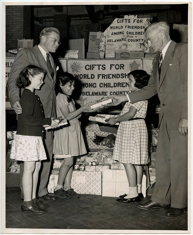 Fascinated kids gaze on as a truckload of Christmas gifts, given by the school children of Delaware County, New York, as a gesture of friendship and goodwill to the children of other nations, and to be sent overseas through the World Friendship Among Children Committee, is received by Reverend Herbert C. Lytle Jr., left, administrative secretary of Church World Service from George Taylor, right, president of the Board of Education of Stamford, New York, during ceremonies held in New York City, October 13, 1948 .RNS archive photo by Lou Pentler. Photo courtesy of the Presbyterian Historical Society.