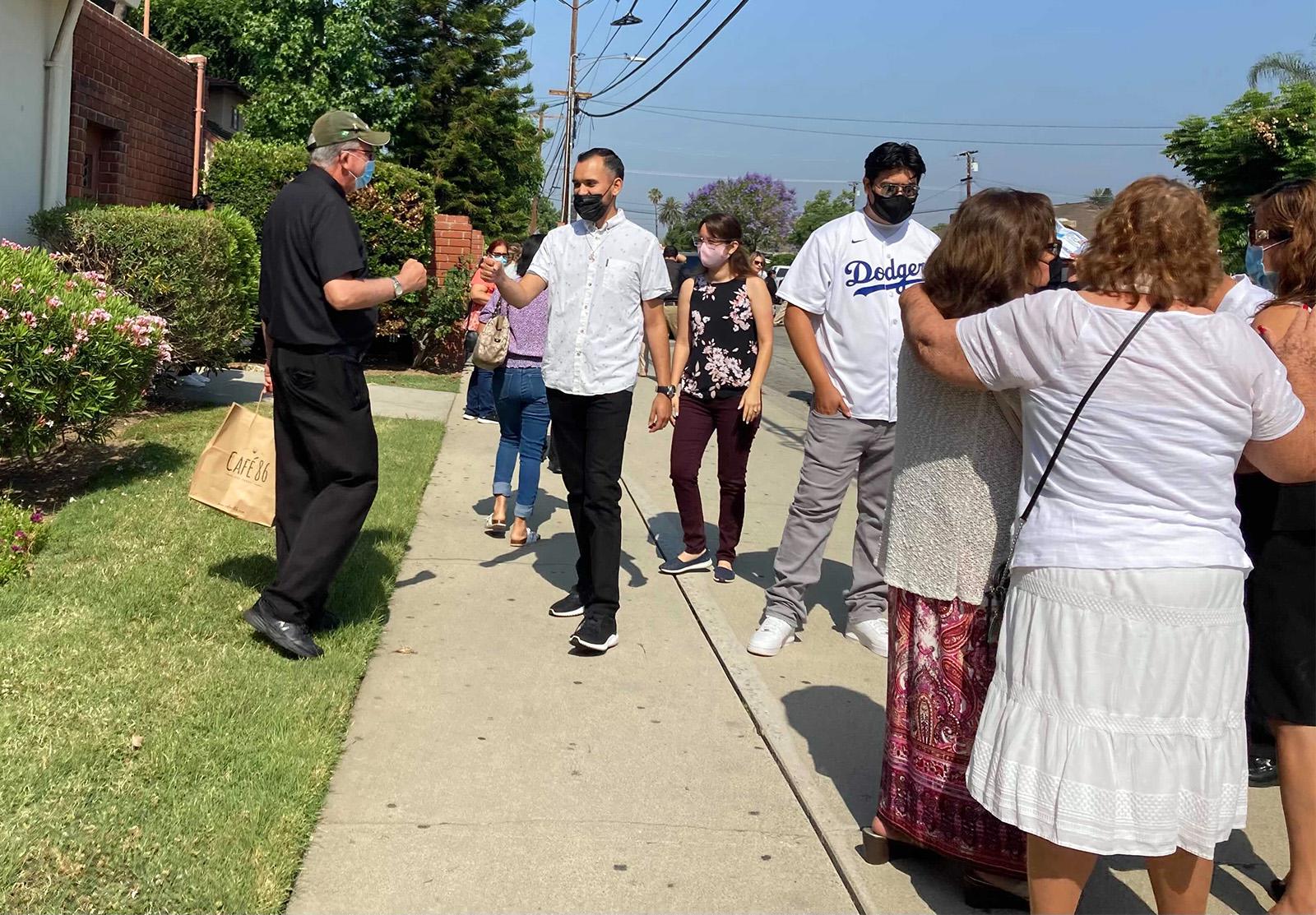 The Rev. Austin Doran, left, fist bumps a St. Anthony Catholic Church parishioner on Sunday, June 20, 2021, in San Gabriel, California. RNS photo by Alejandra Molina