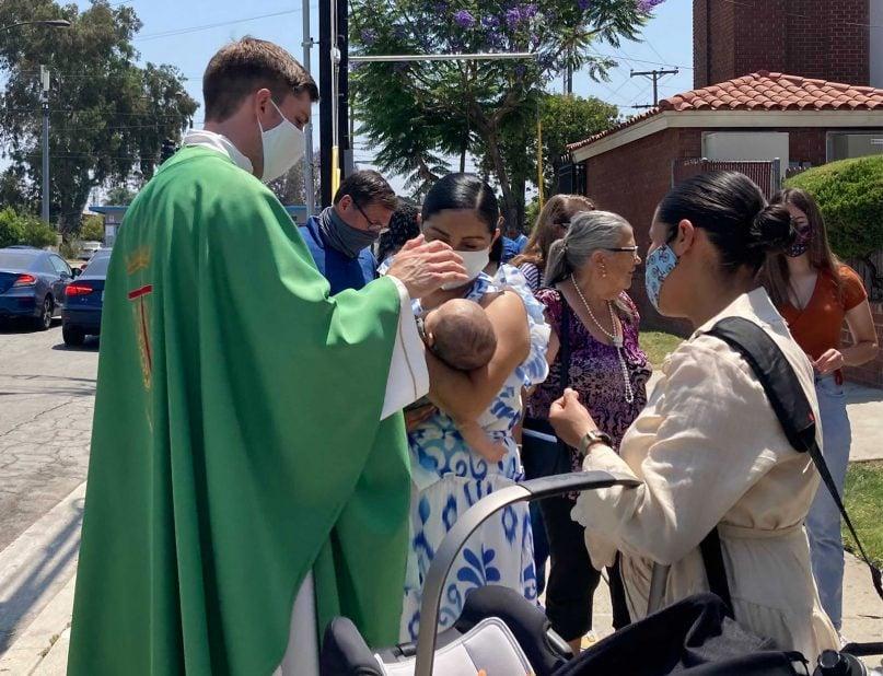 The Rev. Matt Wheeler, left, blesses Alejandra Prendergast's son after an indoor Mass at St. Anthony Catholic Church, Sunday, June 20, 2021, in San Gabriel, California. RNS photo by Alejandra Molina