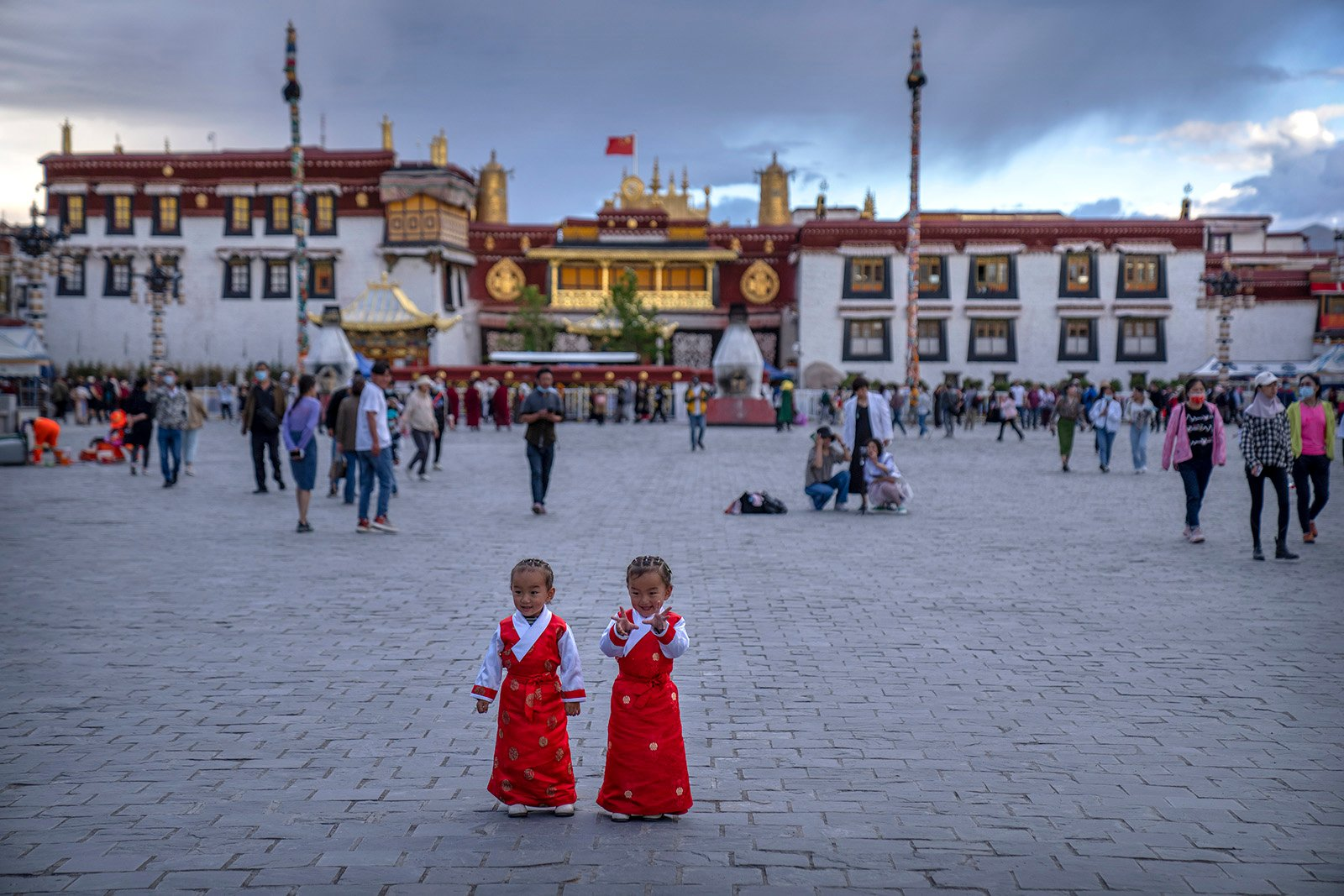 Girls stand on a square in front of the Jokhang Temple in Lhasa in western China's Tibet Autonomous Region, as seen during a government organized visit for foreign journalists, Tuesday, June 1, 2021. (AP Photo/Mark Schiefelbein)