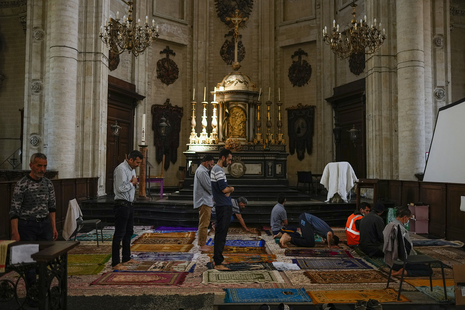 Muslim worshippers on hunger strike pray as they occupy the Saint-Jean-Baptiste-au-Beguinage church in Brussels, Monday, June 7, 2021. Dozens of migrants without official papers and who have been occupying the church since last February, with permission of the priest, began a hunger strike on May 23, 2021, to draw the attention of Brussels authorities to their plight. (AP Photo/Francisco Seco)