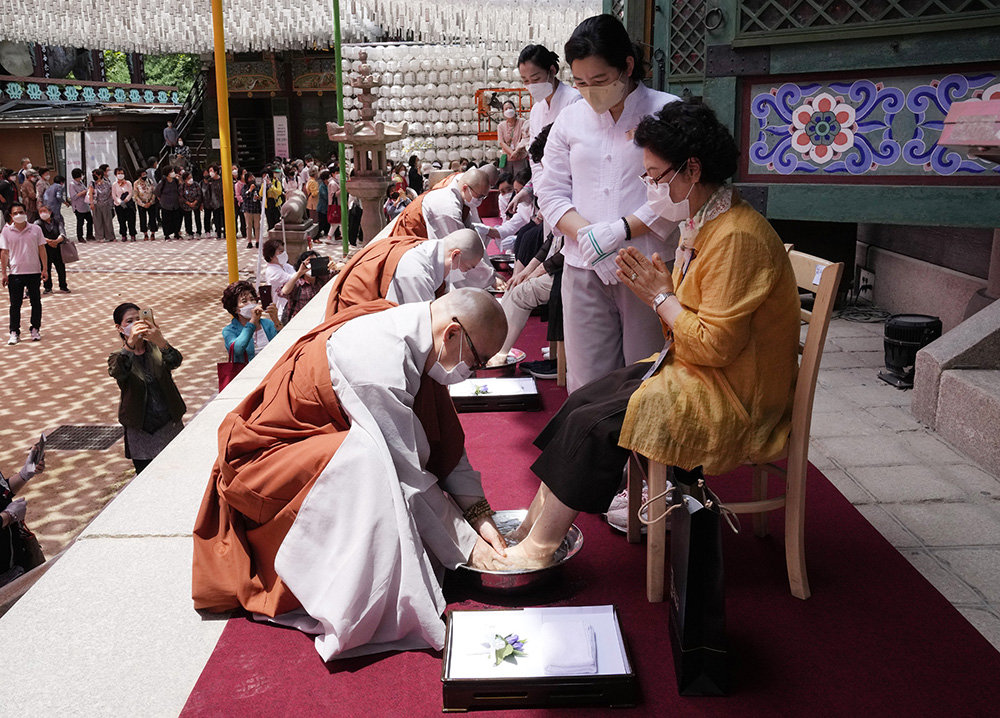 A Buddhist monk washes the feet of a woman, praying for her longevity, during a service to mark Dano, a Korean traditional holiday that falls on the fifth day of the fifth month of the lunar calendar, at the Jogye Temple in Seoul, South Korea, Monday, June 14, 2021. The Korean holiday marks the beginning of the summer season and is a day to pray for favorable weather for farming and fishing and a good fall harvest. (AP Photo/Ahn Young-joon)