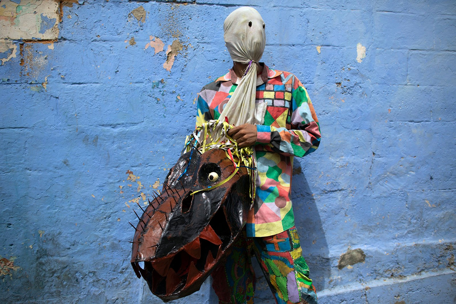 A man dressed in a devil costume holds his mask during a celebration marking the Catholic holiday of Corpus Christi in Naiguata, Venezuela, Thursday, June 3, 2021. Carrying masks of animals and sea monsters, residents of all ages dance in the ritual known as Dancing Devils, which symbolizes the triumph of good over evil. (AP Photo/Ariana Cubillos)