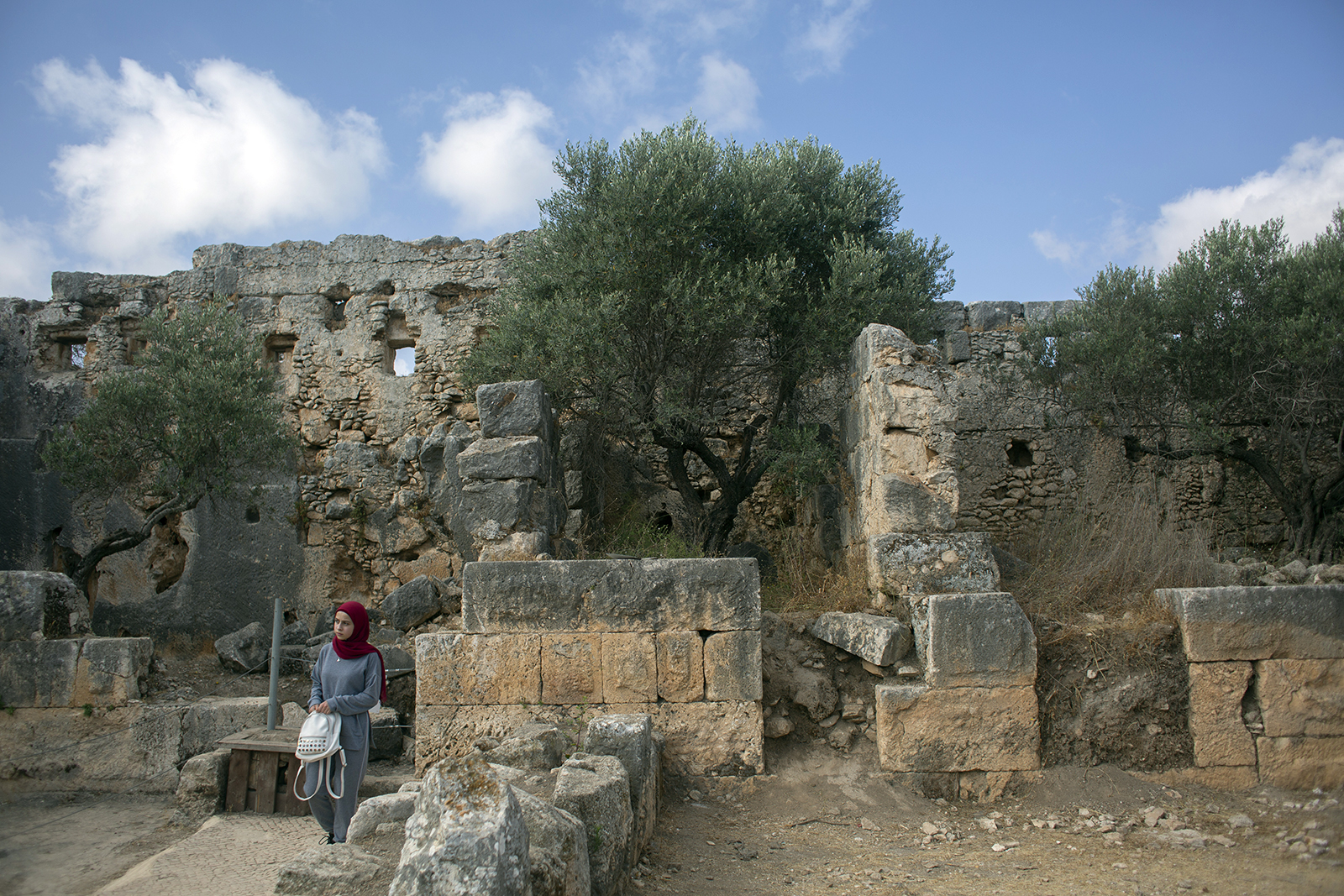 """A hiker explores Deir Qalaa, """"Monastery of the Castle,"""" the remains of a Byzantine monastery near the Jewish settlement of Peduel and the Palestinian village of Deir Balout, west of the West Bank city of Salfit, Friday, June. 11, 2021. A growing number of Palestinians are taking up hiking, which offers a way to explore the countryside and historical landmarks in the Israeli-occupied West Bank. (AP Photo/Nasser Nasser)"""