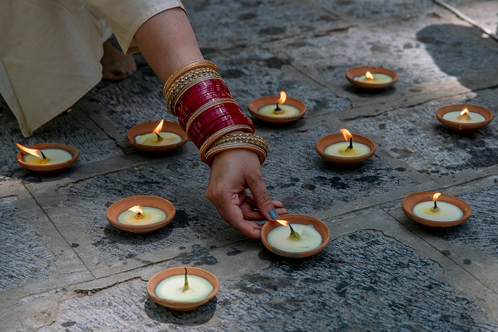 A Kashmiri Hindu lights earthen lamps during the annual festival at the Kheer Bhawani Hindu temple in Tulla Mulla, northeast of Srinagar, Indian controlled Kashmir, Friday, June 18, 2021. Hundreds of Hindu devotees attended the prayers in the historic Kheer Bhavani Temple during the annual festival dedicated to Hindu goddess Durga. (AP Photo/ Dar Yasin)