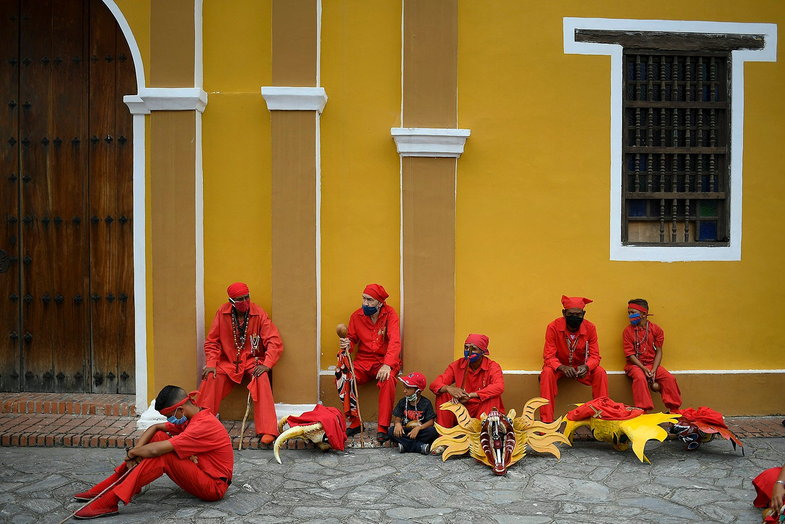 Dancing devils sit outside a local Catholic church listening to the Mass taking place inside, in San Francisco de Yare, Venezuela, Thursday, June 3, 2021, amid the coronavirus pandemic. The Carnival-like dance, in which the devils pay penance and ask for relief from physical ailments, symbolizes the ongoing struggle between good and evil. The tradition dates to 1742, when liberal priests in Venezuela used it to include African slaves who were not permitted to worship in the same church as their white masters.(AP Photo/Matias Delacroix)