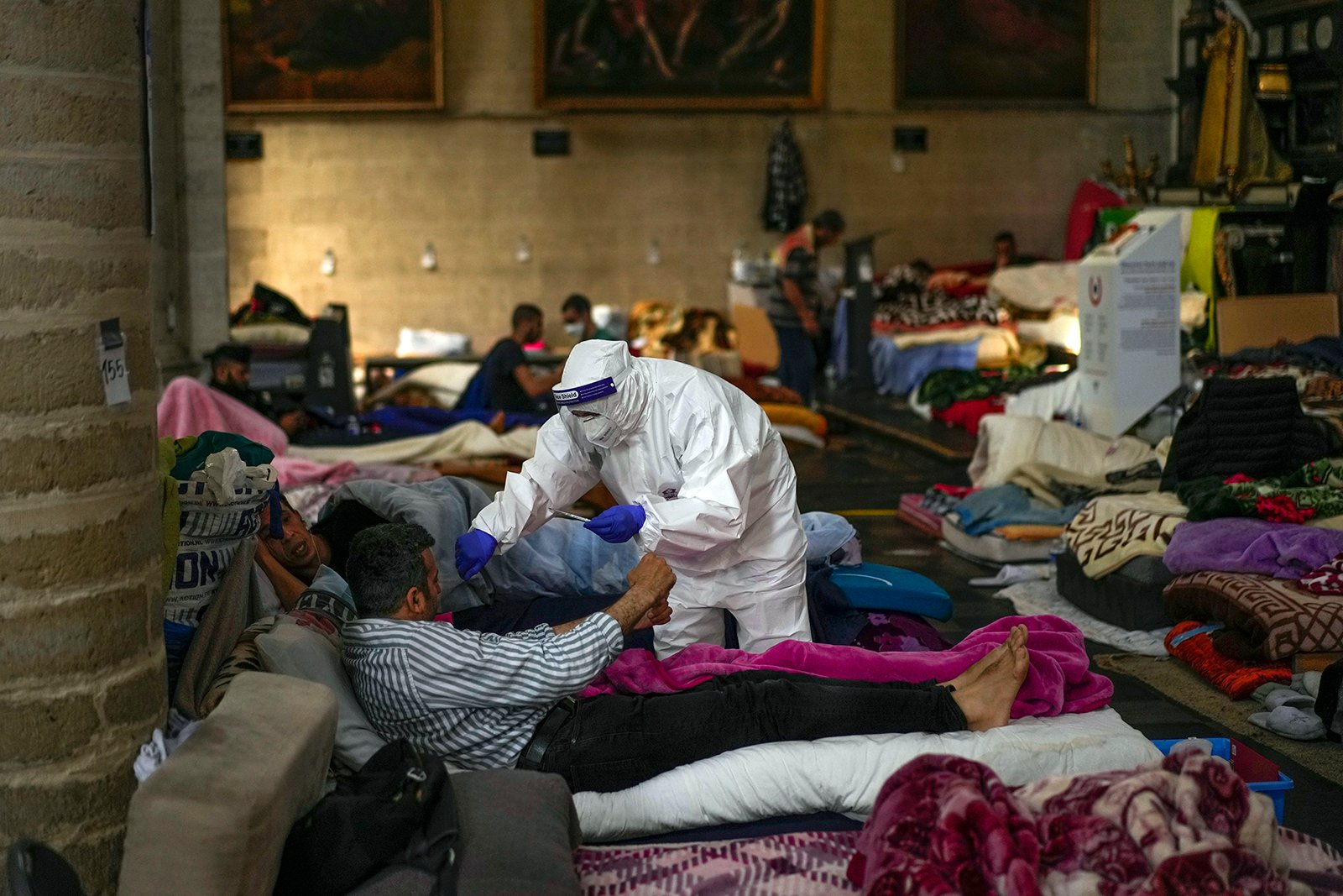 A Red Cross health worker attends a man on hunger strike as he occupies the Saint-Jean-Baptiste-au-Beguinage church in Brussels, Monday, June 7, 2021. Dozens of migrants without official papers who have been occupying the church since last February, with permission of the priest, began a hunger strike on May 23, 2021, to draw the attention of Brussels authorities to their plight. (AP Photo/Francisco Seco)