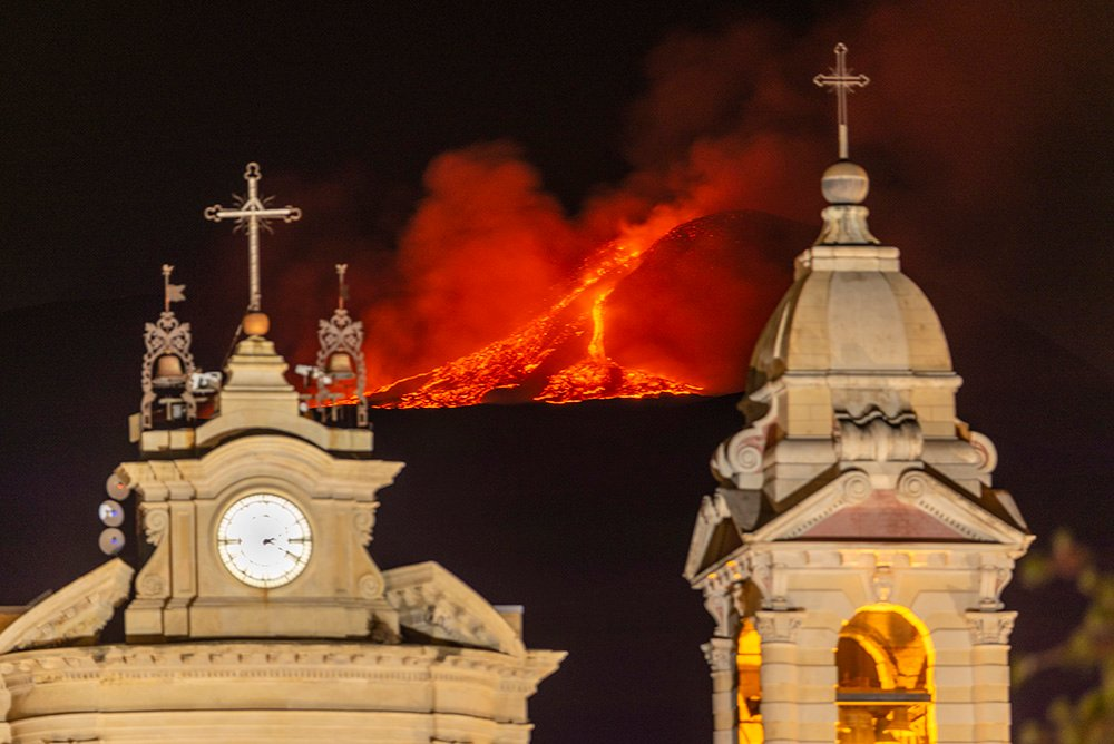 Lava erupts from a crater of Mt. Etna, Europe's largest active volcano, behind Santa Maria della Guardia church in Belpasso, near Catania, in the southern Italian island of Sicily, early Friday, June 18, 2021. Since Feb. 16, 2021, Mt. Etna has begun a series of spectacular eruptive episodes. (AP Photo/Salvatore Allegra)