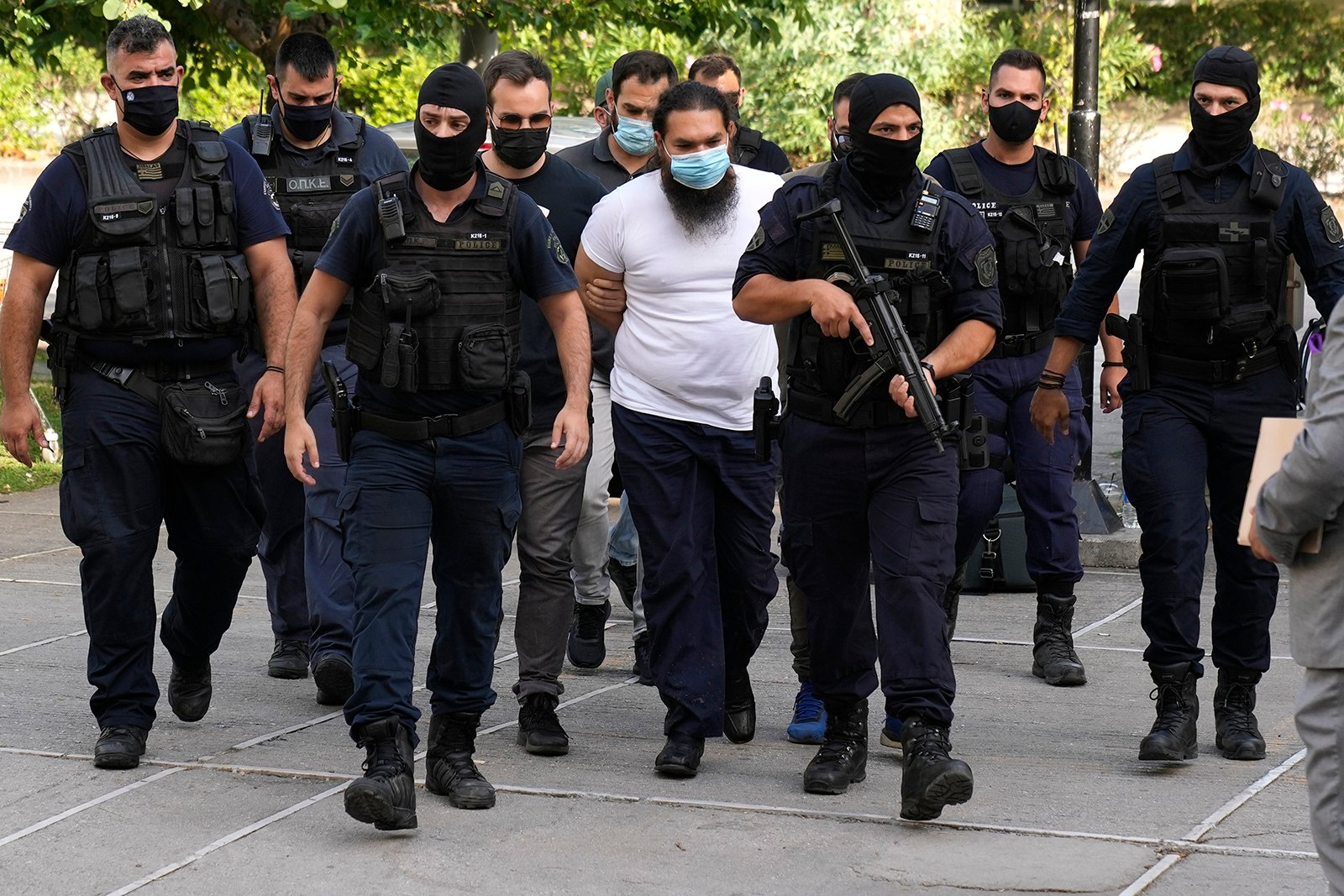 Police escort a suspect, in the center, to the prosecutor's office in a court in Athens, Greece, Thursday, June 24, 2021. The defrocked Greek Orthodox priest has been charged with several counts of causing serious bodily harm following an acid attack that injured seven senior bishops and three others.  (AP Photo / Petros Giannakouris)