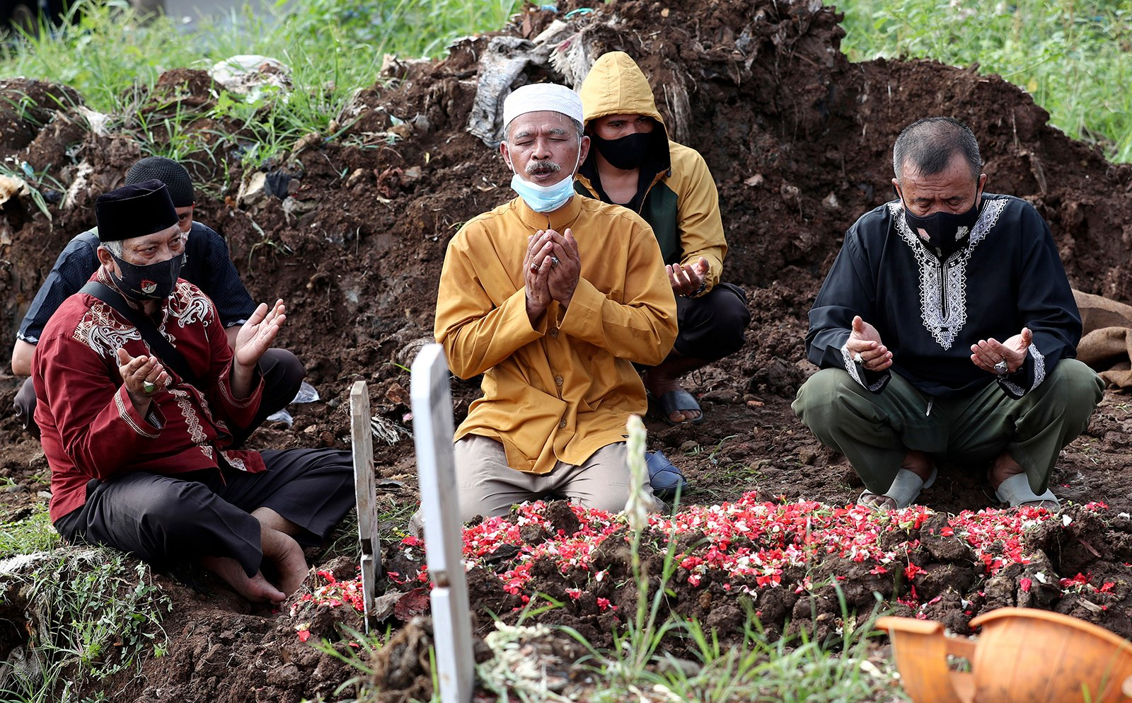 Family members pray during the burial of their relative at a section of Srengseng Sawah Cemetery reserved for those who died of COVID-19, in Jakarta, Indonesia, Wednesday, June 9, 2021. The world's fourth-most populous country, with about 275 million people, has reported more coronavirus cases than any other Southeast Asian country. (AP Photo/Tatan Syuflana)
