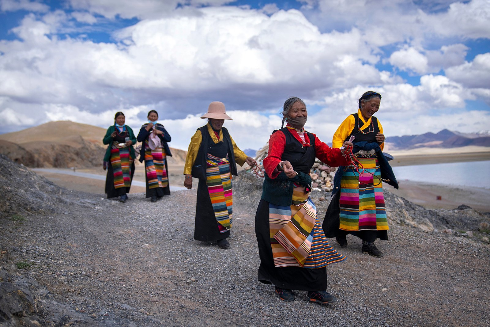 Tibetan women circumnavigate a Buddhist religious site in Namtso in western China's Tibet Autonomous Region, as seen during a government organized visit for foreign journalists, Wednesday, June 2, 2021. (AP Photo/Mark Schiefelbein)
