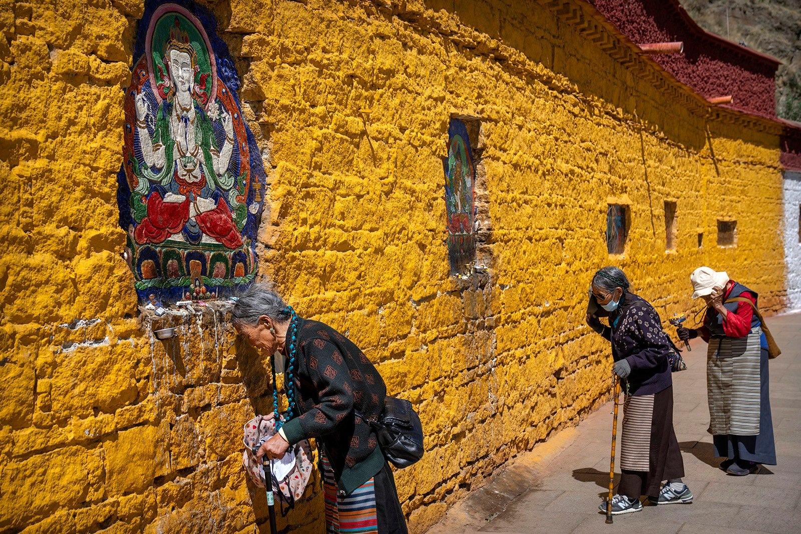 Buddhist faithful pray outside the Potala Palace in Lhasa in western China's Tibet Autonomous Region, as seen during a government organized visit for foreign journalists, Tuesday, June 1, 2021. (AP Photo/Mark Schiefelbein)
