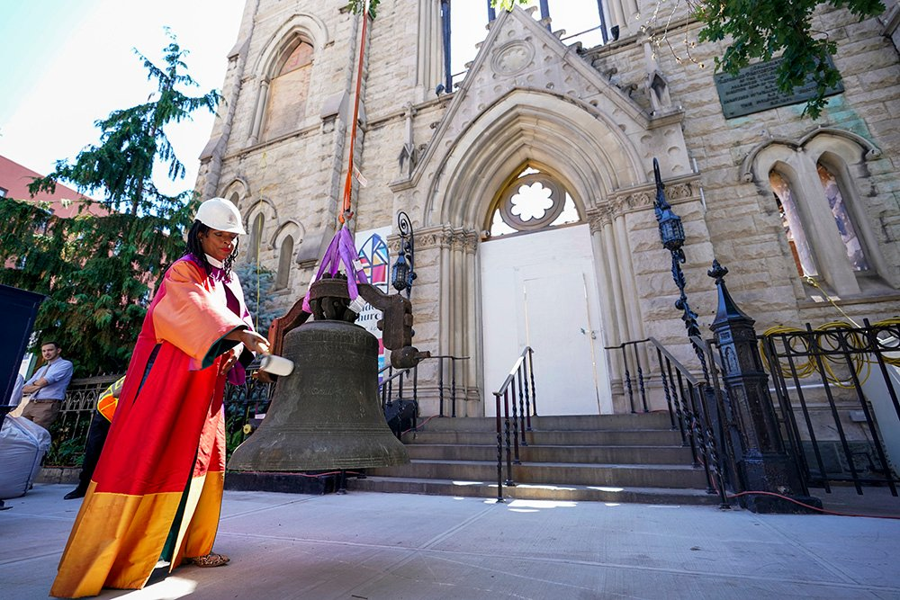 Senior Minister Rev. Jacqueline J. Lewis rings New York's Liberty Bell after a construction crew lowered it from Middle Collegiate Church's bell tower on Wednesday, June 16, 2021, in the East Village neighborhood of New York. The bell was discovered intact in the historic church after it was gutted by a six-alarm fire in December 2020. It will be displayed at the New York Historical Society while middlechurch.org/rising works on funding a campaign to rebuild the church and return the bell to it's place. (AP Photo/Mary Altaffer)