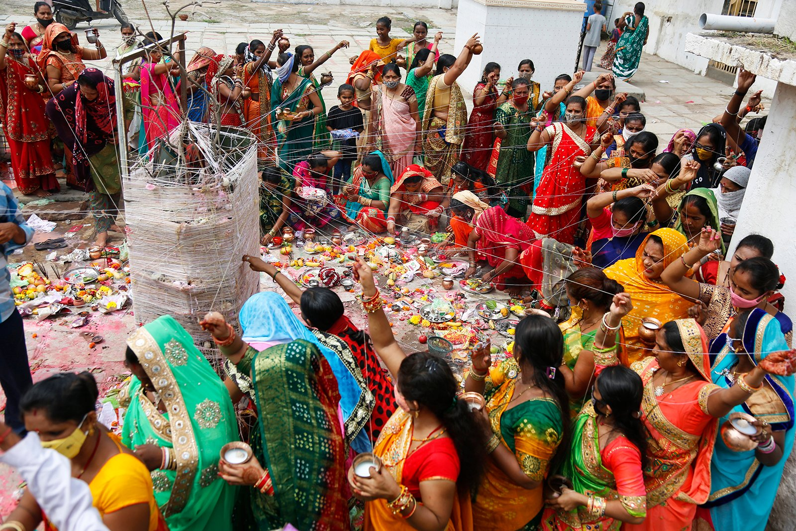 Married Hindu women perform rituals around a banyan tree during the Vat Savitri festival in Ahmedabad, India on Thursday, June 24, 2021. Vat Savitri is celebrated on a full moon day when women pray for the longevity of their husbands.  (AP Photo / Ajit Solanki)