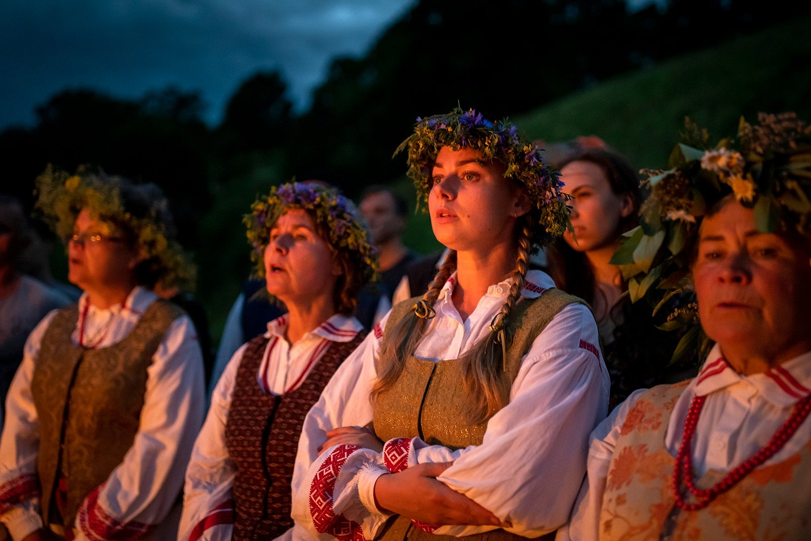 Women wearing flower crowns and traditional Lithuanian outfits sing songs during a celebration of Midsummer Day and the summer solstice in the small town of Kernave, northwest of the capital Vilnius, Lithuania, Wednesday, June 23, 2021. Midsummer or Midsummer, the shortest night of the year, is filled with magic - the festivities include making wreaths of oak leaves and jumping over the flames, and young people are encouraged to go out and look for fern flowers.  (AP Photo / Mindaugas Kulbis)