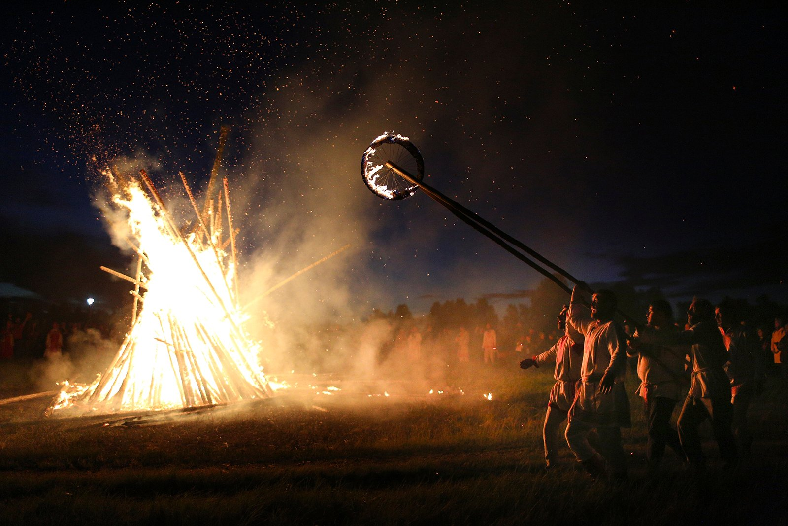 People walk around a bonfire celebrating the summer solstice in Okunevo village, northeast of the Siberian city of Omsk, Russia, Monday, June 21, 2021. The festivities of Ivan Kupala, or John the Baptist, are similar to Mardi Gras and reflect pre-Christian Slavic traditions and practices. (AP Photo/Evgeniy Sofiychuk)