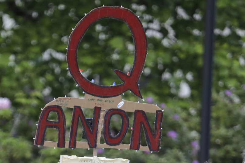 FILE - In this May 14, 2020, file photo, a person carries a sign supporting QAnon during a protest rally in Olympia, Washington. (AP Photo/Ted S. Warren, File)