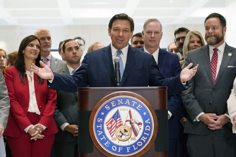 Surrounded by lawmakers, Florida Gov. Ron DeSantis speaks at the end of a legislative session, Friday, April 30, 2021, at the Capitol in Tallahassee, Florida. (AP Photo/Wilfredo Lee)