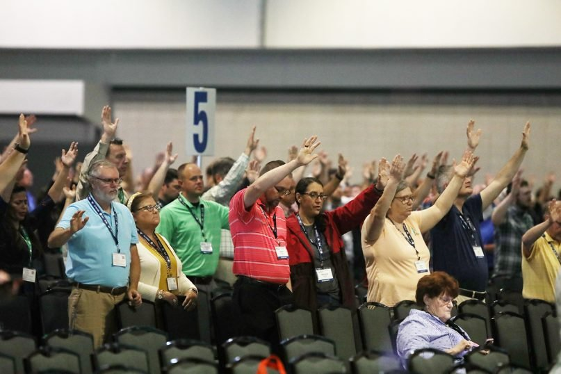 Messengers raise their hands in prayer at the Southern Baptist Convention annual meeting on June 16, 2021, in Nashville, Tennessee. RNS photo by Kit Doyle