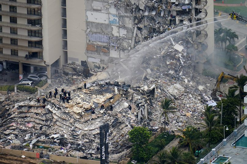 Rescue workers work in the rubble at the Champlain Towers South Condo, Friday, June 25, 2021, in Surfside, Florida. The apartment building partially collapsed on Thursday. (AP Photo/Gerald Herbert)