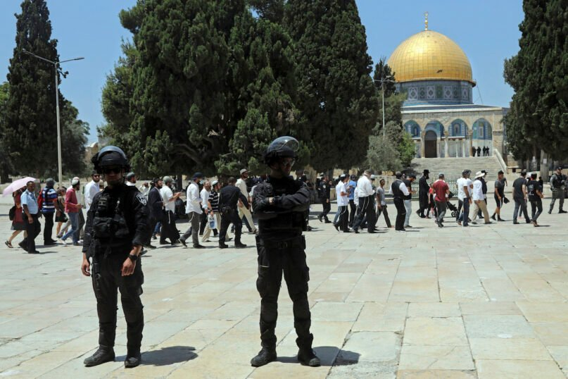 Israeli police officers stand guard as Jewish men visit the Dome of the Rock Mosque in the Al-Aqsa Mosque compound in the Old City of Jerusalem during the mourning ritual of Tisha B'Av (Ninth of Av) fasting and a memorial day, commemorating the destruction of ancient Jerusalem temples, Sunday, July 18, 2021. (AP Photo/Mahmoud Illean)