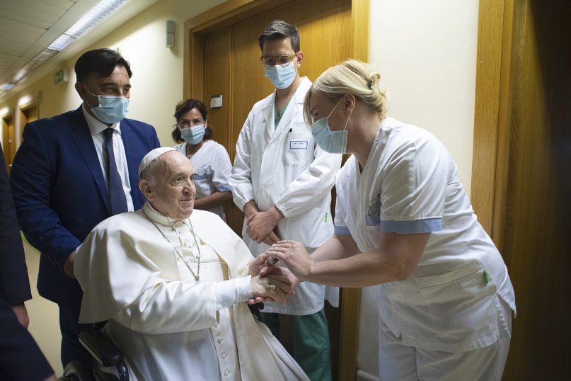 Pope Francis is greeted by hospital staff July 11, 2021, as he sits in a wheelchair inside the Agostino Gemelli Polyclinic in Rome, where he was hospitalized for intestinal surgery. The first international trip scheduled for the pope after his recent surgery is set to be Slovakia in September. (Vatican Media via AP)