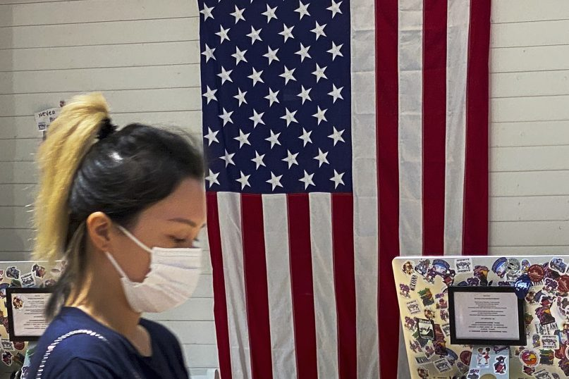 """A woman walks by a counter displaying an American flag at a fashion boutique in Beijing, July 11, 2021. China on Sunday said it will take """"necessary measures"""" to respond to the U.S. blacklisting of Chinese companies over their alleged role in abuses of Uyghur people and other Muslim ethnic minorities. (AP Photo/Andy Wong)"""
