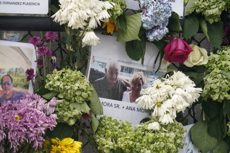 This June 29, 2021, photo shows a memorial wall for the victims of the Champlain Towers South building collapse in Surfside, Fla., with a photo of Juan Mora Sr. and his wife, Ana Mora. (AP Photo/Gerald Herbert)
