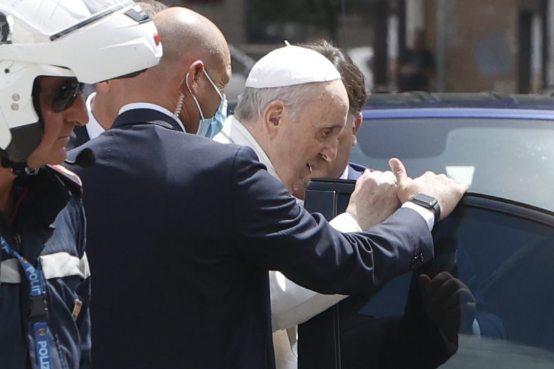 Pope Francis stops on July 14, 2021, to greet police who escorted him as he arrived at the Vatican after leaving the hospital, 10 days after undergoing surgery to remove half his colon. Francis had half of his colon removed for a severe narrowing of his large intestine on July 4, his first major surgery since he became pope in 2013. (AP Photo/Riccardo De Luca)