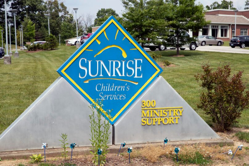 FILE - In this May 26, 2021 file photo, A sign for Sunrise Children's Services sits in front of the agency in Mount Washington, Ky. Kentucky reached a contract deal Thursday, July 15, 2021 to continue placing youngsters with a Baptist-affiliated children's agency, coming after the Democratic governor's administration removed LGBTQ anti-discrimination language that the agency steadfastly refused to sign (Brandon Porter/Kentucky Today via AP, File)
