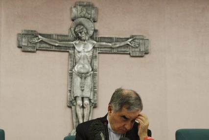In this Sept. 25, 2020, file photo, Cardinal Angelo Becciu looks down as he meets the media during a news conference in Rome. The Vatican's criminal tribunal indicted 10 people July 3, 2021, including Becciu, and four companies on charges including extortion, abuse of office and fraud in connection with the secretariat of state's 350 million-euro investment in a London real estate venture. Becciu helped engineer the initial London investment when he was the chief of staff in the secretariat of state. (AP Photo/Gregorio Borgia, File)