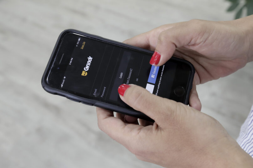 In this May 29, 2019, file photo, a woman looks at the Grindr app on her mobile phone in Beirut. With few rules in the U.S. guiding what companies can do with the vast amount of information they collect about what webpages people visit, the apps they use and where they carry their devices, there's little stopping similar spying activity targeting politicians, celebrities and just about anyone who's a target of another person's curiosity. (AP Photo/Hassan Ammar, File)