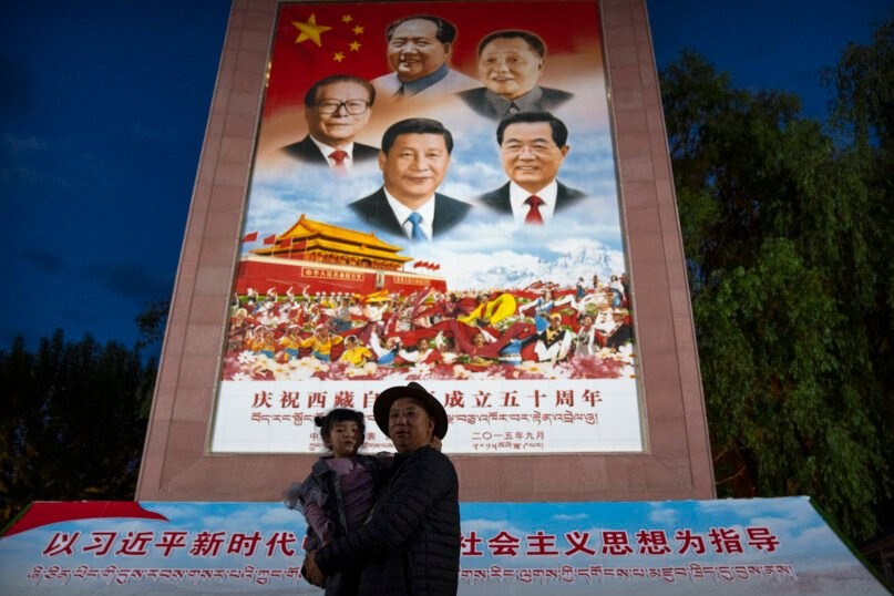 A man holds a girl as they pose for a photo in front of a large mural depicting Chinese President Xi Jinping, bottom center, and other Chinese leaders at a public square at the base of the Potala Palace in Lhasa in western China's Tibet Autonomous Region on June 1, 2021. Xi has made a rare visit to Tibet as authorities tighten controls over the Himalayan region's traditional Buddhist culture, accompanied by an accelerated drive for economic development and modernized infrastructure. (AP Photo/Mark Schiefelbein)