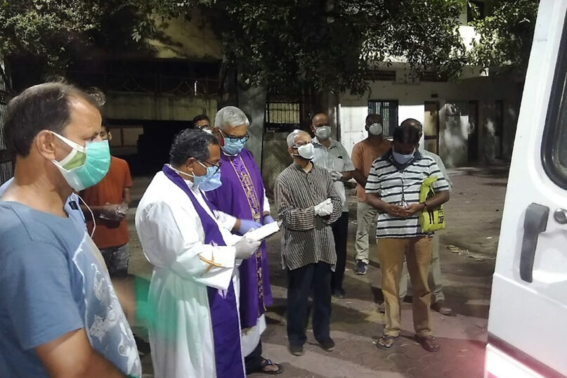 In this April 18, 2021, photo provided by the Rev. Cedric Prakash, priests pray over the body of the late Rev. Jerry Sequeira before his cremation in Ahmedabad, India. Sequeira is one of more than 500 Catholic priests and nuns who have died from COVID-19 in India according to the Rev. Suresh Mathew, a priest at Holy Redeemer's Church in New Delhi and the editor of the church-run Indian Currents magazine. (Cedric Prakash via AP)