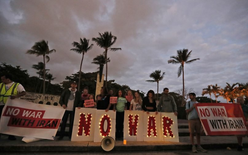 Anti-war demonstrators hold signs at the Torch of Friendship monument, Thursday, Jan. 9, 2020, in Miami. (AP Photo/Wilfredo Lee)