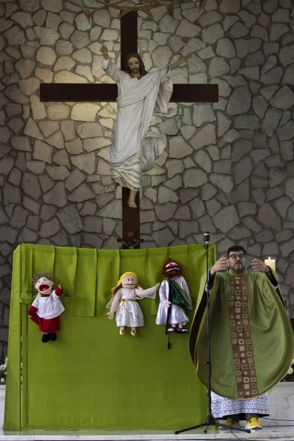 Catholic Priest Carlos Cardona delivers his homily during Mass, next to his puppets, from left, Monsi, an altar boy, Angelita, an angel, and Saint Judas Thaddeus, at the Saint Judas Thaddeus church in Huixquilucan, Mexico City, Sunday, June 27, 2021. For the last 21 years, Father Cardona has been using puppets to help bring in more children to Sunday services. (AP Photo/Marco Ugarte)