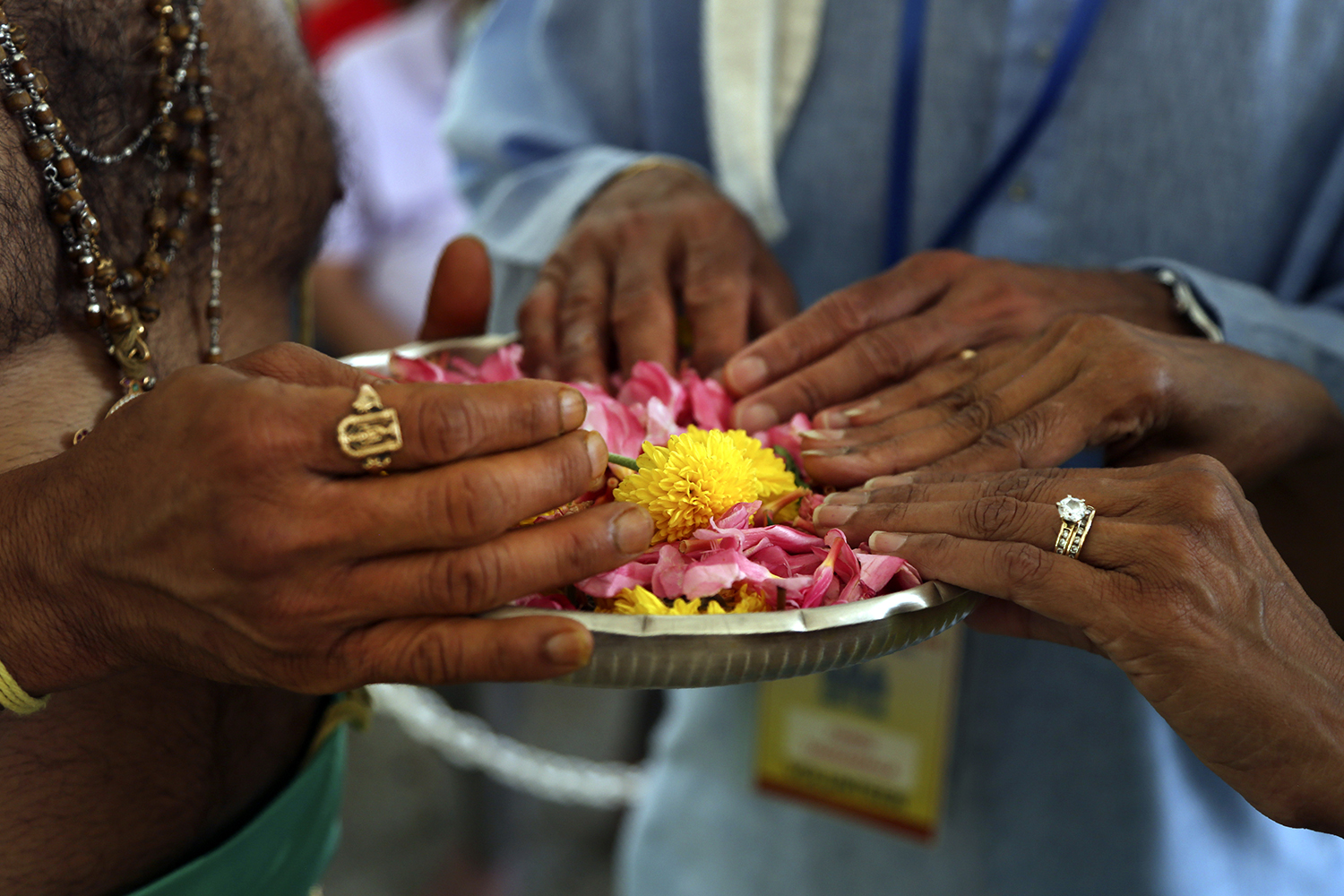 Hindu priest Gopala Dhattar, left, gives blessings to Pandu Tadikamalla, center, and his wife, Rama Tadikamalla, right, as they rest their hands on a bed of flower petals during the Maha Kumbhabhishekam, a five-day rededication ceremony at the Sri Venkateswara Temple in Penn Hills, Pa, Friday, June 25, 2021. Built in the 1970s, the Sri Venkateswara Temple is the oldest major Hindu temple in the country. Maha Kumbhabhishekams occur about every 12 years and involve ceremonies to reenergize the temple and its deities. (AP Photo/Jessie Wardarski)