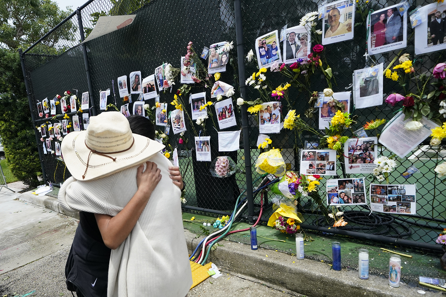 People embrace at a make-shift memorial outside St. Joseph Catholic Church, in Surfside, Fla., Monday, June 28, 2021, near the collapsed building for people still missing or dead. Many people were still unaccounted for after Thursday's fatal collapse. (AP Photo/Gerald Herbert)