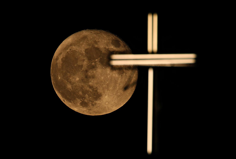 The moon rises over the cross of St. Joseph Church in Baghdad, Iraq, Friday, June 25, 2021. (AP/Photo/Hadi Mizban)