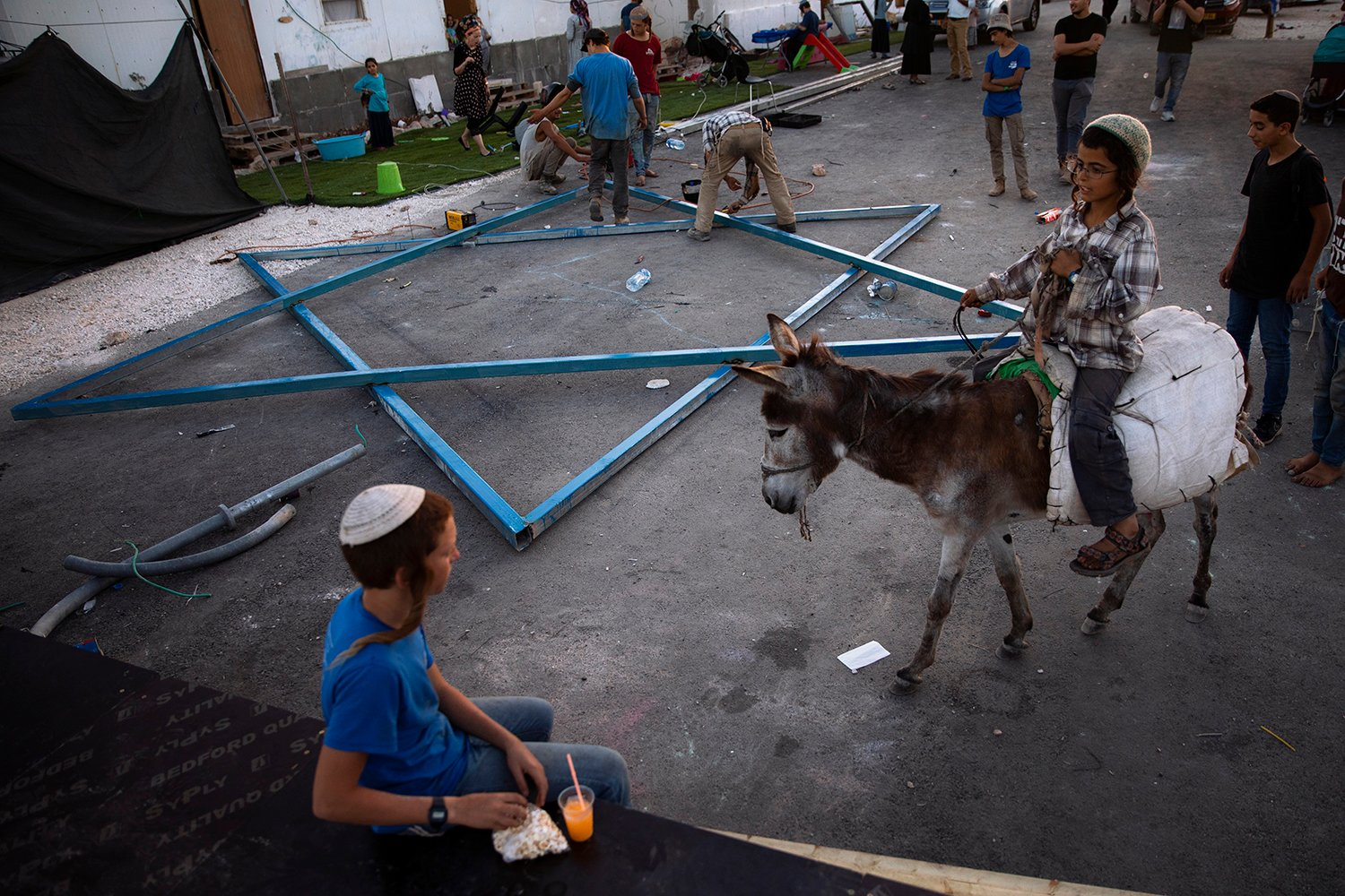 An Israeli settler rides a donkey as others build large Star of David in the recently established wildcat outpost of Eviatar near the West Bank city of Nablus, Thursday, July 1, 2021. Israel has reached a compromise with Jewish settlers which they will leave by the end of the week and the area will become a closed military zone, but the houses and roads will remain in place. (AP Photo/Oded Balilty)