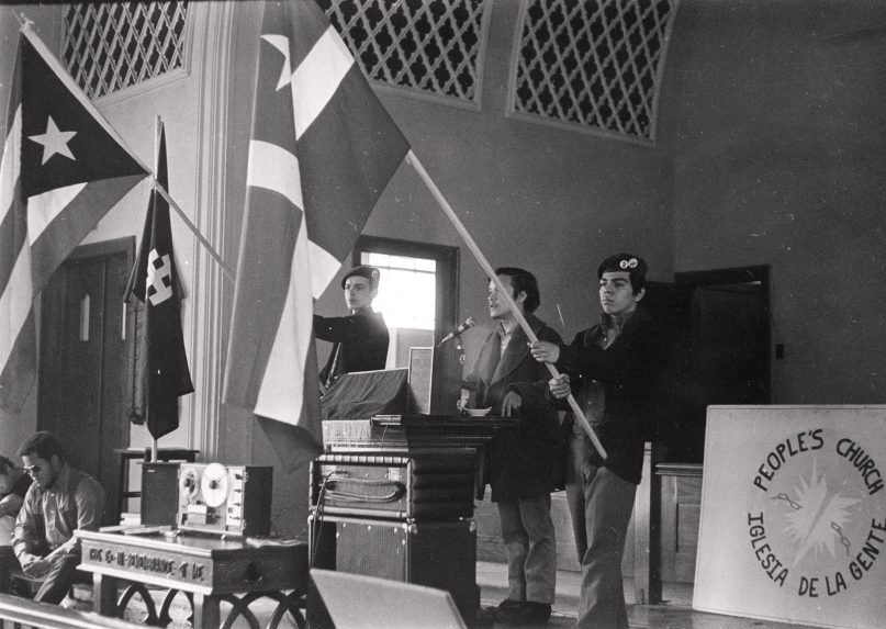 Young Lords members hold flags inside the Armitage Methodist Church in Chicago in March 1970, commemorating the Masacre de Ponce. Photo © Carlos Flores