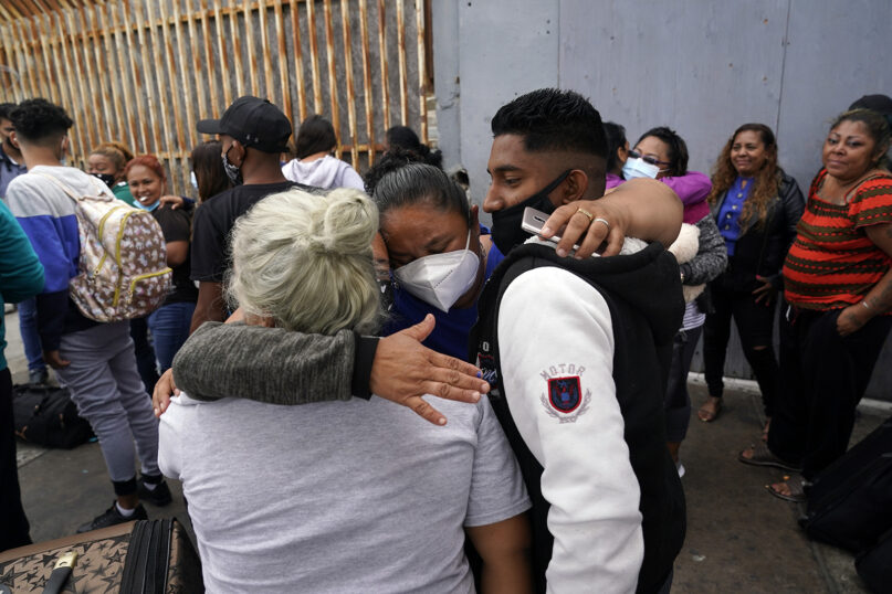 Alex Cortillo, right, of Honduras gets a hug from Erika Valladares Ponce, also of Honduras, center, and others, as he waits to cross into the United States to begin the asylum process July 5, 2021, in Tijuana, Mexico. Dozens of people are allowed into the U.S. twice a day at a San Diego border crossing, part of a system that the Biden administration cobbled together to start opening back up the asylum system in the U.S. Immigration advocates have been tasked with choosing which migrants can apply for a limited number of slots to claim humanitarian protection. (AP Photo/Gregory Bull)