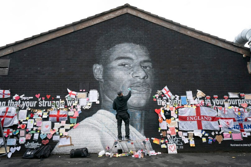 Street artist Akse P19 repairs the mural of Manchester United striker and England player Marcus Rashford on the wall of the Coffee House Cafe on Copson Street, in Withington, Manchester, England, July 13, 2021. The mural was defaced with graffiti in the wake of England losing the Euro 2020 soccer championship final match to Italy, but subsequently covered with messages of support by well-wishers. (AP Photo/Jon Super)