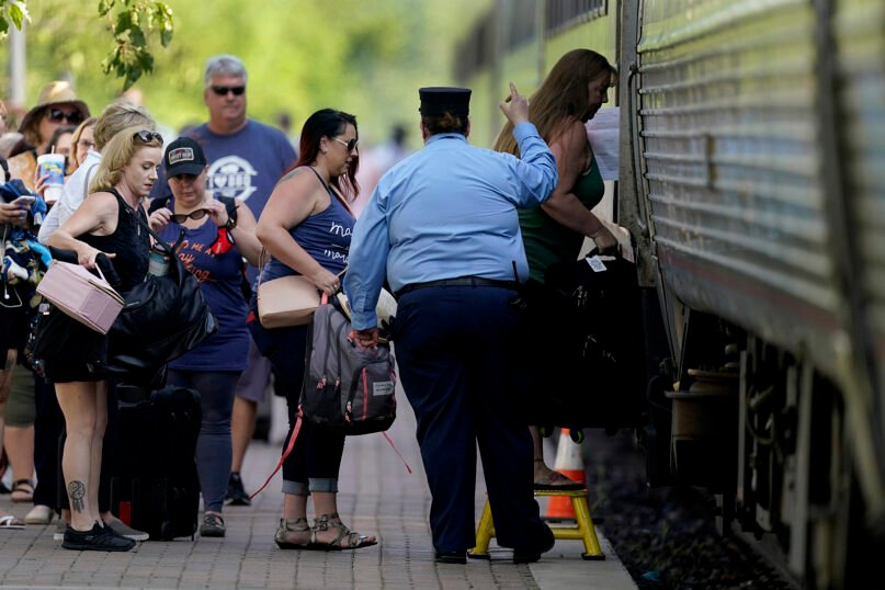 In this June 11, 2021, file photo, passengers board a Missouri River Runner Amtrak train in Lee's Summit, Missouri. As the U.S. emerges from the COVID-19 crisis, Missouri is becoming a cautionary tale for the rest of the country: It is seeing an alarming rise in cases because of a combination of the fast-spreading delta variant and resistance among many people to getting vaccinated. (AP Photo/Charlie Riedel, File)