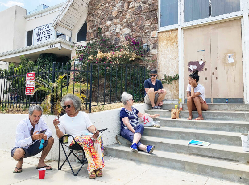 From right, Stephanie Serra and her husband Chase Cole sit at the top of the steps of First Baptist Church of Venice while talking to Ingrid Mueller, center, on Sunday, July 11. Naomi Nightingale, left, speaks with a visitor from her lawn chair before returning to the conversation. The group meets here Sundays to discuss ways to preserve the abandoned church building. RNS photo by Alejandra Molina
