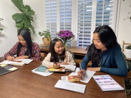 The Cariaga family sits together to work on letter writing. Photo courtesy of Jehovah's Witness