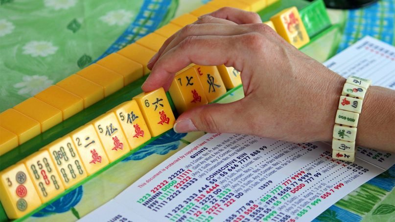 This May 31, 2013, file photo shows a woman handling mahjong tiles during a baby boomer game night gathering in Mayfield Village, Ohio. (AP Photo/Bonnie Gruttadauria)