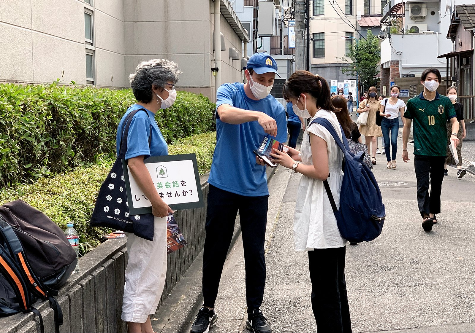 Pierce Hite, center, a Southern Baptist Convention International Mission Board missionary serving in Tokyo, Japan, explains a gospel tract to a woman, July 20, 2021. Hite and missionary Julie Bradford, left, took part in an outreach event called 5-Minute English that provides opportunities for people to practice conversational English on the street. Photo courtesy of the IMB